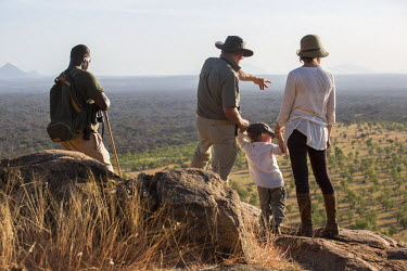 KEN9428 Kenya, Meru. A young family and their guide look out over Meru National Park during a walking safari.