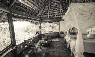 Kenya, Meru. A woman looks out over Meru National Park from her luxury room at Elsa's Kopje. MR.