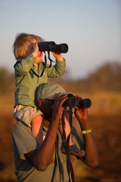 KEN9437 Kenya, Meru. A young boy and a guide search for wildlife in Meru National Park.
