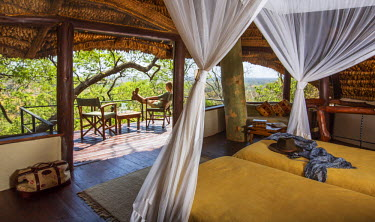 Kenya, Meru. A lady relaxes on the balcony of her luxury safari room. MR.