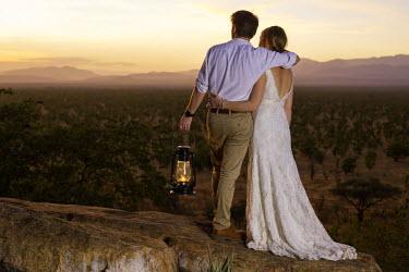 KEN9450 Kenya, Meru. A young newly-wed couple watch the sun set over Meru National Park. MR.