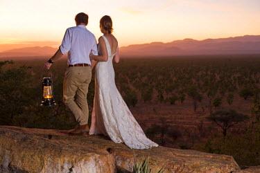 KEN9451 Kenya, Meru. A young newly-wed couple watch the sun set over Meru National Park. MR.