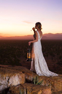 KEN9454 Kenya, Meru. A new bride enjoys a glass of Champagne, watching the sun set over Meru National Park. MR.