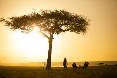 KEN9513 Kenya, Mara North Conservancy. A couple enjoy a sundowner on the plains of the Mara North Conservancy. MR.