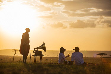 KEN9576 Kenya, Mara North Conservancy. A couple enjoy a sundowner in the Mara, listening to music from a vintage Gramophone. MR.