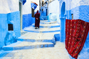 MOR2208AW A man in traditional djellaba walking the blue-washed streets of Chefchaouen, Morocco