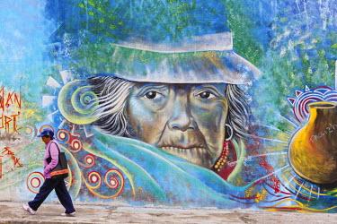 HMS2103885 Ecuador, Imbabura, Atuntaqui, Ecuadorian busy modern woman in front of a wall graffiti depicting a traditional Andean woman