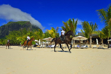 MTS0011AW Horse riders on the beach in front of a  luxury hotel on the Le Morne Peninsula,  Mauritius, Indian Ocean