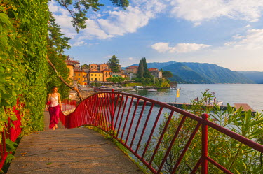ITA4313AW Varenna, Como lake, Lombardy, Italy. Woman with red dress walking on the lake front.