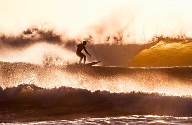 ARRAJA000082 surfer in heavy surf at dusk