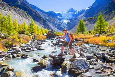 ARBOME000039 A female hiker crossing a river in the Swiss Alps. In the background is the Ried glacier. This region of Wallis, close to Zermatt, is a paradise for outdoor enthusiasts like climbers, alpinists, hiker...