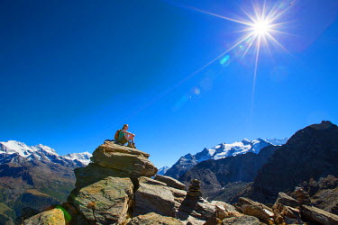 ARBOME000048 A female hiker sitting on top of the Wannihorn in the Swiss Alps. In the background the four thousand meter peaks of the Weisshorn and Weissmies. This region of Wallis is a outdoor paradise for all cl...