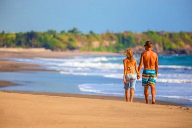 ARTRKO000332 Couple are walking on the beach in Bali. Indonesia