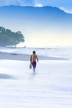 CR33039AW Central America, Costa Rica, Puntarenas, Nicoya peninsula, a male surfer on a beach near Santa Teresa (MR)