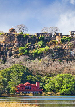 IND7722 India, Rajasthan, Ranthambhore.  The Jogi Mahal Forest Guest House in Ranthambhore National Park with the ancient ruins of Ranthambhore Fort on top of the escarpment.