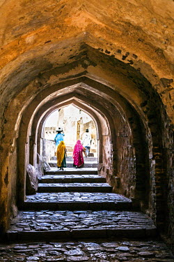 IND7742 India, Rajasthan, Ranthambhore.  Villagers walk through an arched passageway in the ancient ruins of the massive walled Ranthambore Fort complex whose foundations were laid in 944AD.