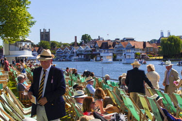 ENG12394 UK, Berkshire, Henley upon Thames. Spectators enjoy the sunshine as they watch the boat race from the Stewards Enclosure at Henley Royal Regatta.
