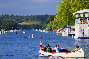 ENG12403 UK, Berkshire, Henley upon Thames. Spectators cruise across the Thames, just beyond the finish line, as a race nears it's climax in the background at Henley Royal Regatta.