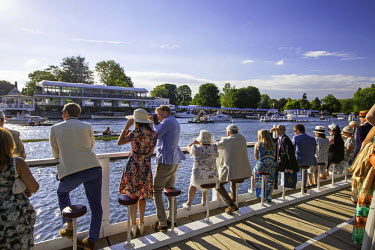 ENG12407 UK, Berkshire, Henley upon Thames. Spectators enjoy the sunshine as they watch the boat race from the sStewards Enclosure at Henley Royal Regatta.