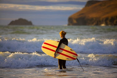 ENG12419 UK, Cornwall, Polzeath. A woman looks out to see, preparing for an evening surf. MR