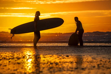 ENG12456 UK, Cornwall, Polzeath. Two women come in from an evening surf against a stunning sunset.