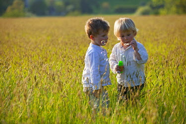 ENG12460 UK, Wiltshire, Marlborough. Two young friends blow bubbles on a summer's evening.
