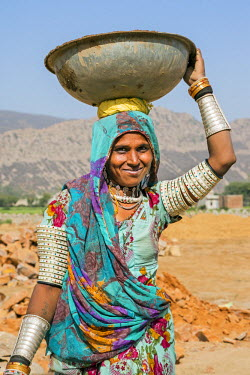 IND7798 India, Jaysamand, Rajasthan.  A Rajasthani woman with numerous bracelets and armbands carries sand on her head to a building site.