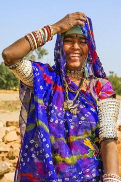 IND7799 India, Jaysamand, Rajasthan.  A happy Rajasthani woman wearing numerous bracelets and armbands.