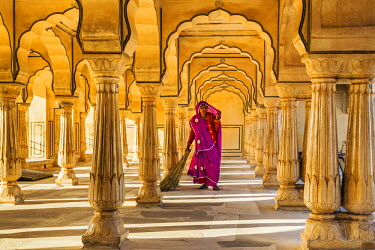 IND7838 India, Rajasthan, Jaipur, Amer.  A Rajasthani woman in bright clothing sweeps the floor of a beautiful pavilion in the magnificent 16th century Amber Fort.