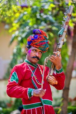 IND7885 India, Rajasthan, Jaipur.  A Rajasthani musician in traditional attire plays a local string instrument called rawan hatha.