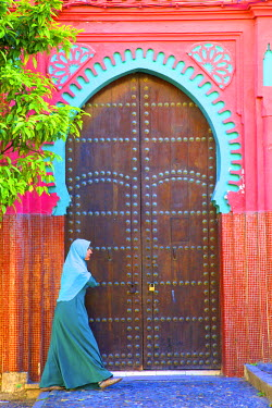 MC03180 Person Walikng Infront Of Traditional Moroccan Decorative Door, Tangier, Morocco, North Africa