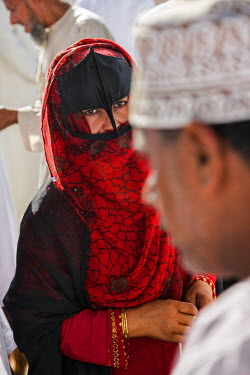 OMA2591 Oman, Ad Dakhiliyah Governorate, Nizwa. A black masked woman at the lively livestock market at Nizwa where local farmers sell goats and cattle. These masks usually denote a woman�s Bedouin heritage.