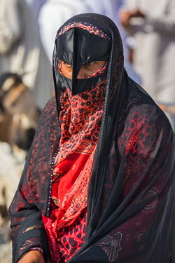 OMA2597 Oman, Ad Dakhiliyah Governorate, Nizwa. A black masked woman at the lively livestock market at Nizwa where local farmers sell goats and cattle. These masks usually denote a woman�s Bedouin heritage.