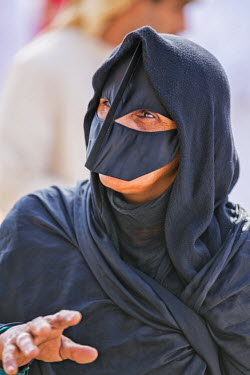 OMA2601 Oman, Ad Dakhiliyah v, Nizwa. A black masked woman at the lively livestock market at Nizwa where local farmers sell goats and cattle. These masks usually denote a woman�s Bedouin heritage.
