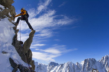 AR3169400031 A mountain climber steps across peaks during his ascent of Alpinisme - Aiguille d'Argentiere, Rhone Alpes, France