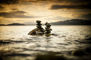 Two small rock stacks are slowly covered by water as the tide rises near Sechelt, BC, Canada.