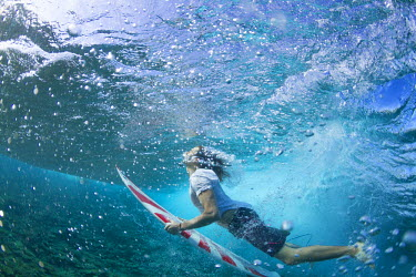 Close up, underwater photo of a surfer duck diving under a wave