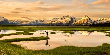 AR4982100022 A man standing near a pond looking torward a mountain range.  Valdez, Alaska, USA.