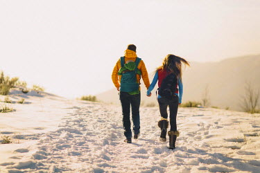 ARADJO000259 A young couple holds hands and hikes against a winter mountain scene and bright sunset. Utah, USA