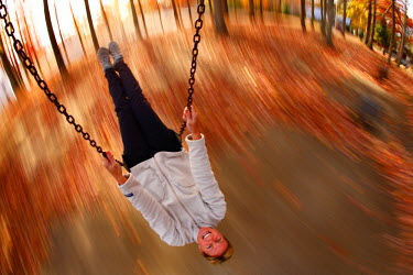 AR3050500003 Swing-mounted remote camera captures a blur motion image of Sarah Chouinard on the swing at the Town Park in Fayetteville, West Virginia, USA