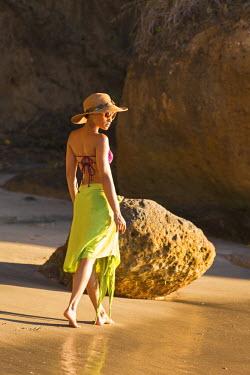 DOM0117AW Dominica, St John Parish, Portsmouth, Secret Bay. A young lady walks along Secret Beach.(MR).
