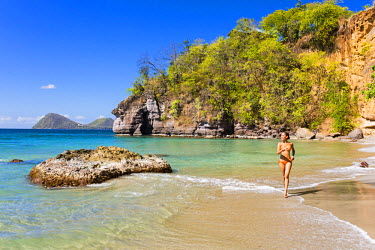 DOM0143AW Dominica, St John Parish, Portsmouth, Secret Bay. A young lady runs along Secret Beach.(MR).