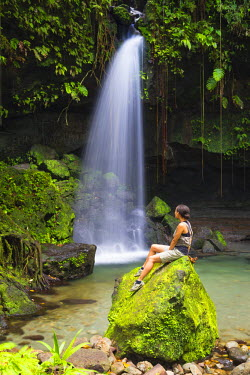 DOM0166AW Dominica, Castle Bruce. A tourst sits on a rock at Emerald Pool. (MR).