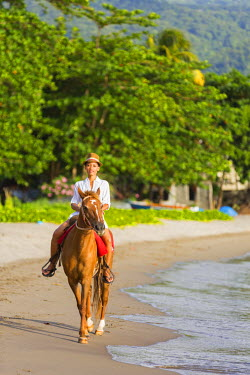 DOM0179AW Dominica, Portsmouth. A young woman rides a horse on Purple Turtle Beach. (MR).