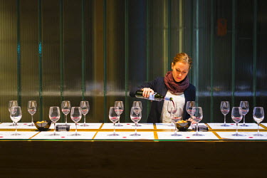 SPA6496AW Spain, Burgos, Gumiel de Izan. A lady pours wine in the Tasting Room at Bodegas Portia, a modern Ribera Del Duero winery designed by Norman Foster architects. (MR).
