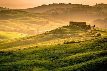 ITA4755AW Val d'Orcia, Tuscany, Italy. A lonely farmhouse with cypress and olive trees, rolling hills.