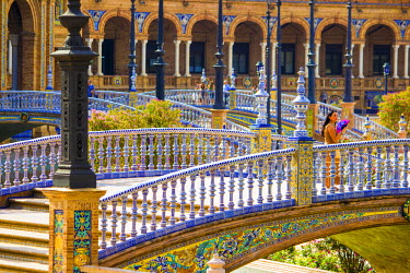 SPA6550AW Spain, Andalucia, Seville Province, Seville, woman with colorful fan watching the horizon, stairs in background, Plaza de Espana