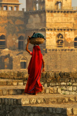 HMS0322751 India, Madhya Pradesh State, Mandu, Jahaz Mahal Palace, built in the 15th century by Ghyas-ud-Din, afghan architectural style, woman carrying her linen on her head in the royal enclave