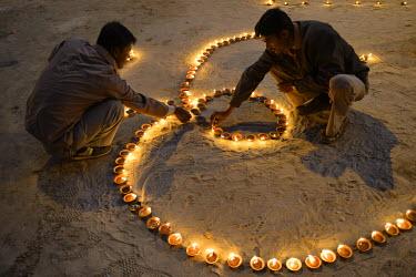 HMS1769611 India, Uttar Pradesh, Varanasi, Dev Deepawali festival, Hindu devotees lighting Om shaped oil lamps The Dev Deepavali festival (litterally the Diwali of the Gods) is celebrated on the full moon of the...
