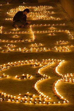 HMS1769773 India, Uttar Pradesh, Varanasi, Dev Deepawali festival, Hindu devotee lighting oil lamps The Dev Deepavali festival (litterally the Diwali of the Gods) is celebrated on the full moon of the Hindu mont...
